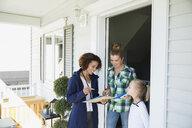 Door to door saleswoman explaining brochure mother daughter - HEROF33223