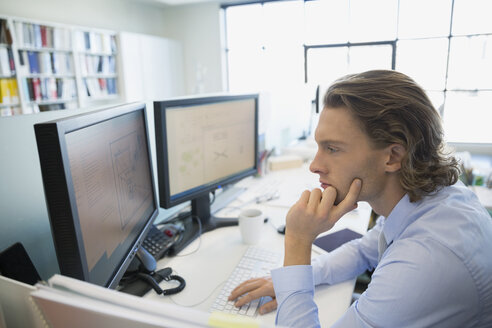 Focused architect working at computer in office - HEROF33229