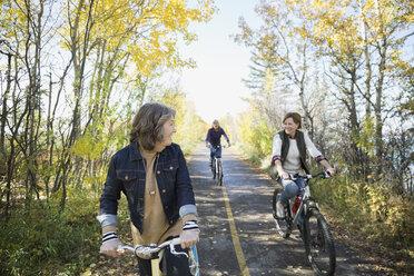 Friends bike riding on autumn path in park - HEROF33235