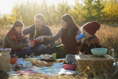 Family enjoying picnic in sunny autumn field - HEROF33241