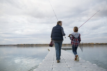Father and daughter fishing on lake jetty - HEROF33268