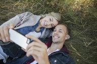 Couple laying in grass taking selfie - HEROF33271