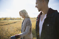Couple walking in sunny autumn field - HEROF33274