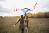 Couple flying a kite in autumn field - HEROF33289