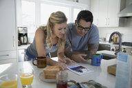 Couple drinking coffee using digital tablet kitchen - HEROF33295