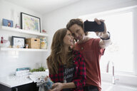 Couple taking selfie in kitchen - HEROF33319