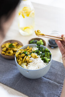 Curry chicken, broccoli and rice, woman eating with chopsticks - GIOF06010