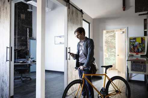 Creative businessman with smart phone and bicycle arriving at office - HEROF33346