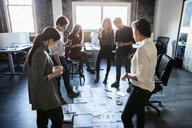 Creative business people meeting, reviewing proofs on loft office floor - HEROF33397
