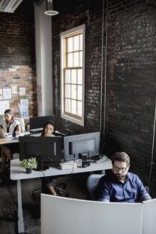Creative business people working at desks in open plan loft office - HEROF33406