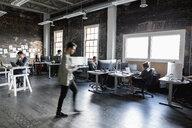 Creative business people working in open plan loft office - HEROF33433
