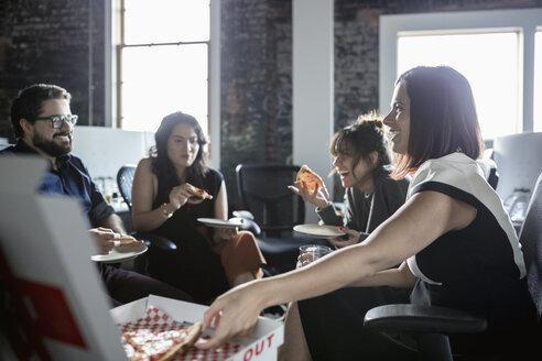 Creative business people enjoying pizza lunch in loft office - HEROF33460