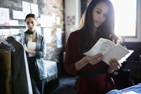 Female fashion designer reviewing dress pattern in office - HEROF33532