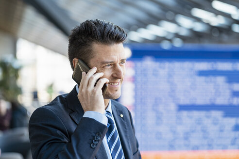 Smiling businessman on cell phone at the station - DIGF06414