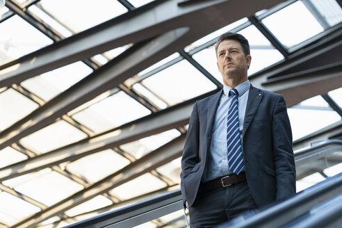 Businessman on escalator - DIGF06417
