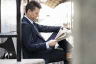Businessman reading newspaper on station platform - DIGF06423