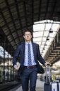 Businessman walking with suitcase on station platform - DIGF06426