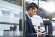 Businessman using cell phone at train station - DIGF06429