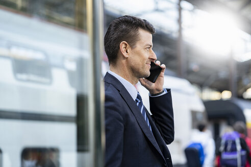 Businessman on cell phone at train station - DIGF06432