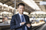 Portrait of smiling businessman using tablet at train station - DIGF06441