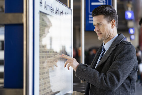 Businessman checking departures board at the train station - DIGF06465