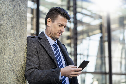 Businessman leaning against a wall using cell phone - DIGF06471