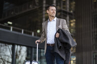 Businessman with suitcase standing outdoors - DIGF06483