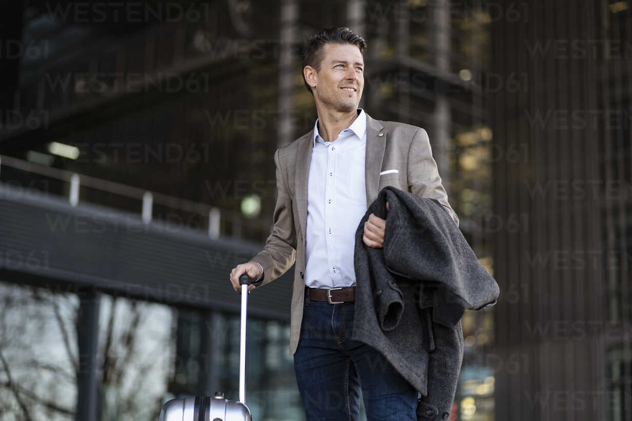 Businessman with suitcase standing outdoors - DIGF06483 - Daniel Ingold/Westend61