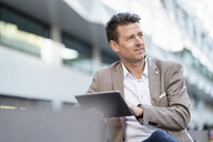 Businessman using tablet outdoors - DIGF06495