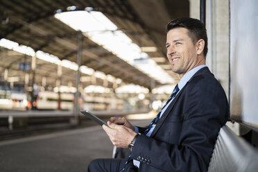 Smiling businessman with tablet waiting on station platform - DIGF06498