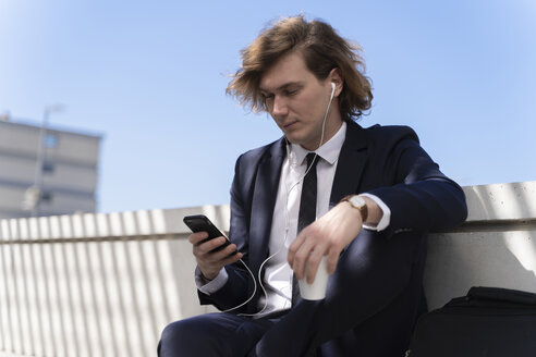 Italy, Florence, young businessman with earphones and smartphone outdoor - FMOF00506