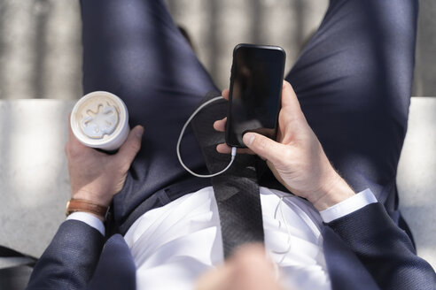 Close-up of businessman with takeaway coffee and smartphone outdoor - FMOF00509