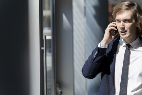 Italy, Florence, young businessman on smartphone outdoor - FMOF00512