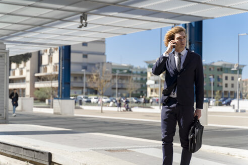 Italy, Florence, young businessman on smartphone outdoor - FMOF00521