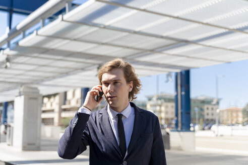 Italy, Florence, young businessman on smartphone outdoor - FMOF00524