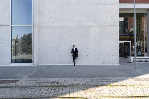 Italy, Florence, young businessman leaning against a building in the city - FMOF00530