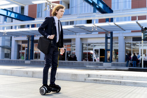 Italy, Florence, young businessman riding hoverboard in the city - FMOF00536