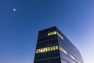 Germany, Stuttgart, lighted windows at modern office building at blue hour - WDF05213
