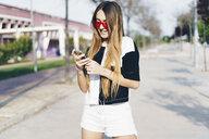 Spain, teenage girl using smartphone on a road - ERRF00829