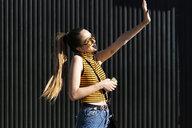Happy teenage girl with earphones and smartphone enjoying the sunshine - ERRF00856