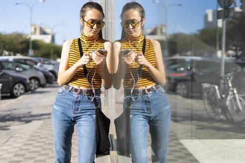 Spain, teenage girl with earphones leaning on a windowpane in sunshine - ERRF00859