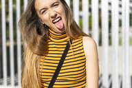 Portrait of teenage girl sticking out tongue - ERRF00862