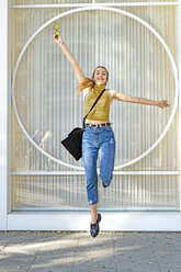 Happy teenage girl jumping in front of a window - ERRF00865