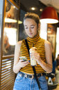 Spain, teenage girl with milk shake using smartphone - ERRF00871