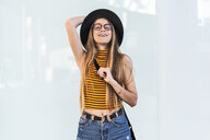 Portrait of happy teenage girl wearing hat and glasses - ERRF00874