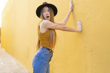 Portrait of surprised teenage girl wearing hat at yellow wall - ERRF00886