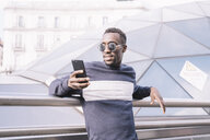 Spain, Madrid, portrait of young man looking at cell phone - OCMF00333