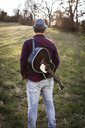 Rear view of man with guitar standing on a meadow - HMEF00271