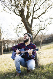 Man playing guitar at a tree on a meadow - HMEF00274