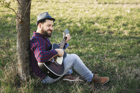 Man playing guitar at a tree on a meadow - HMEF00277